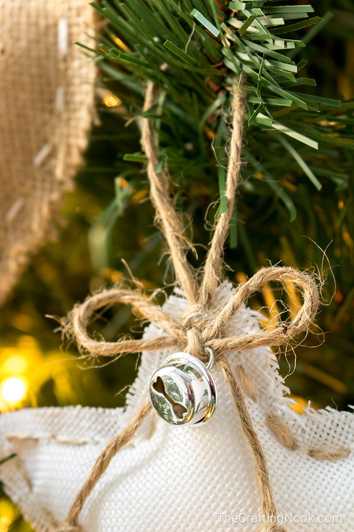 a cute bow made with twine and a jingle bell aganst the white burlap