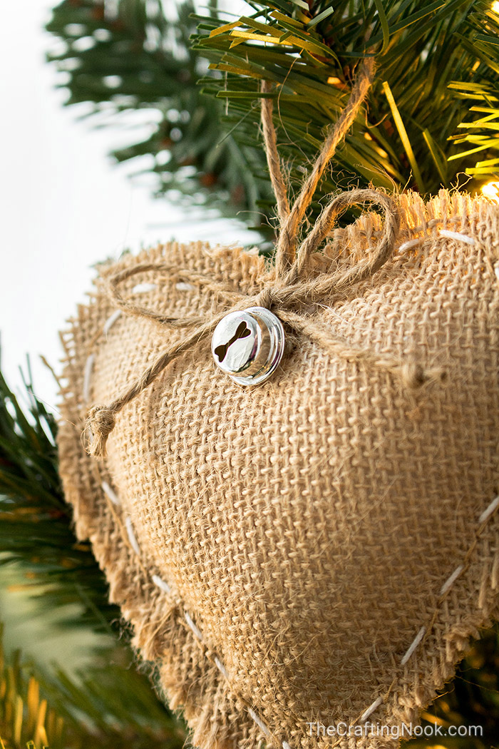 A closeup of the twine bow and jingle bell on the rustic heart