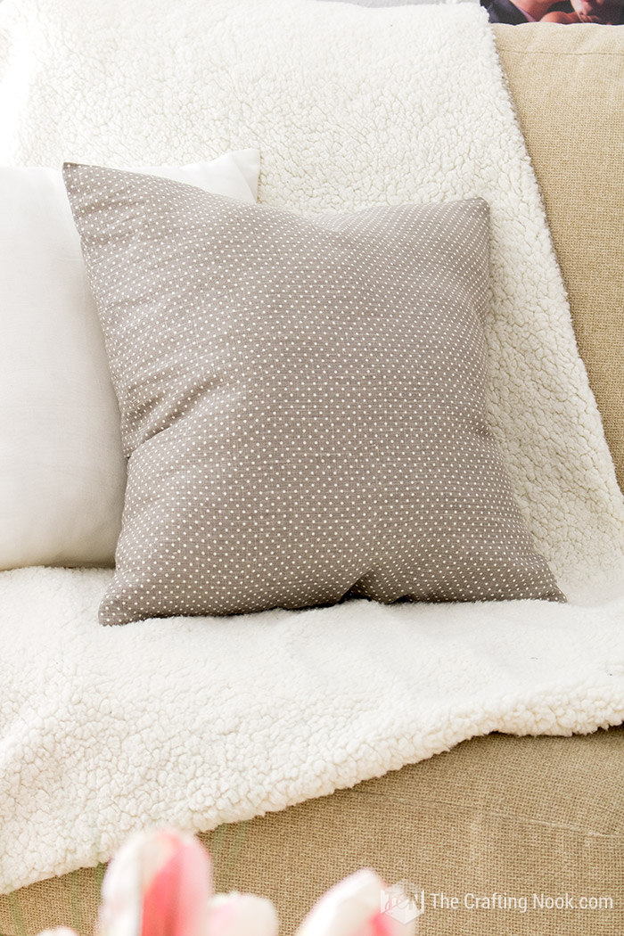 The finihed envelope pillow cover styled on my sofa with cozy blankest and other pillows