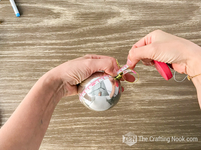 Measuring the bauble with a measuring tape