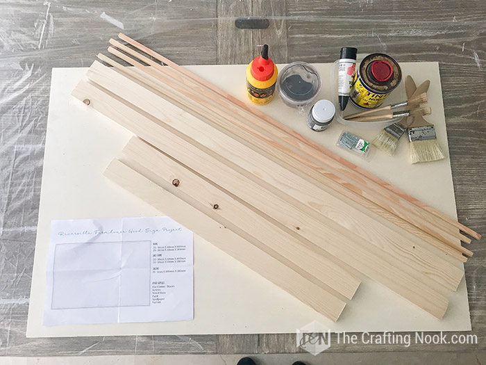 All the supplies gather together for the rustic wood sign