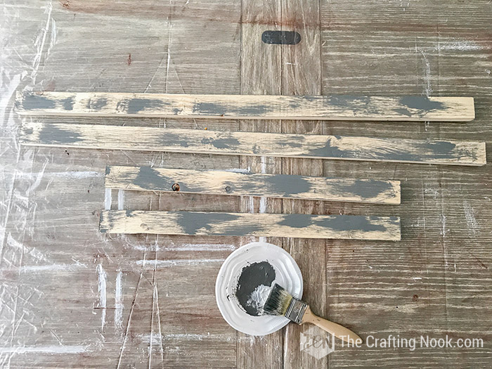 rustic wood sign frame boards painted with rough strokes of grey paint.