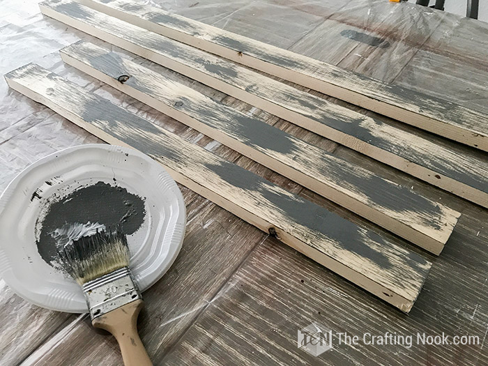 rustic wood sign frame boards painted with rough strokes of grey paint in a different angle