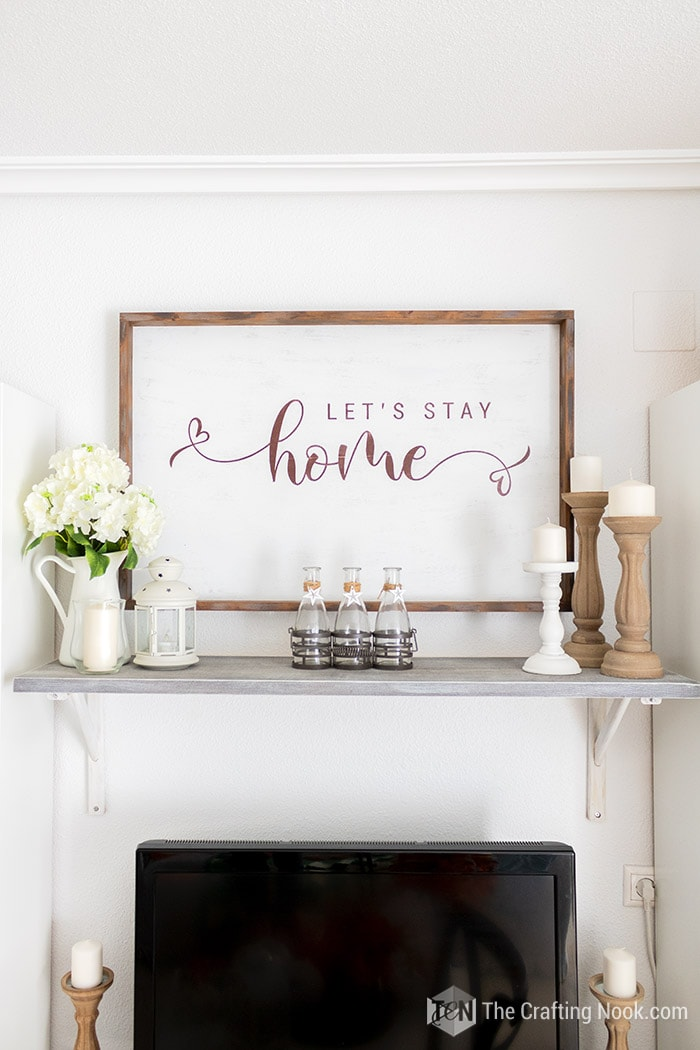 Front view of Rustic wood sign on the wall withLet's Stay Home sentiment.
