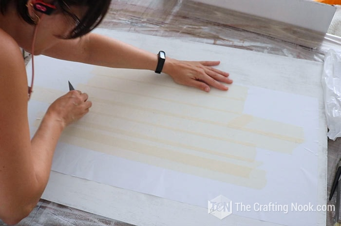 Placing the stencil on the board and secure with a scrapper.