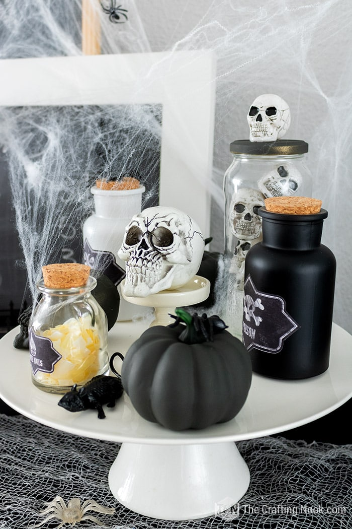 Potion Bottles, skulls and pumpkins on a cake stand. Fall Halloween decor