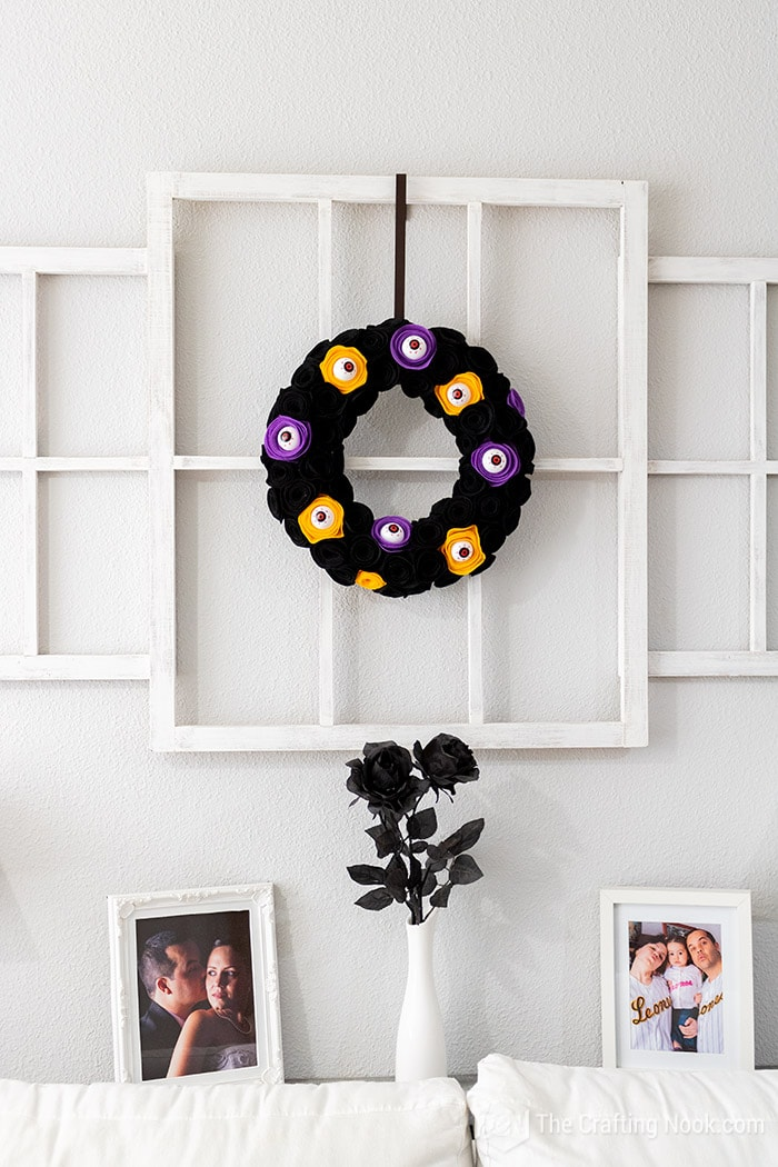 The spooky Halloween Wreath made with spooky eyeballs hanging on the window frame of the living room