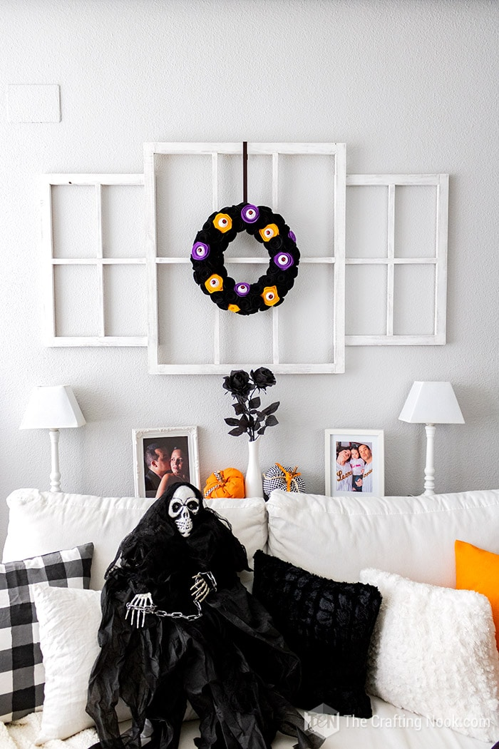 Halloween decor with the Spooky Wreath and a Halloween skull siting on the sofa